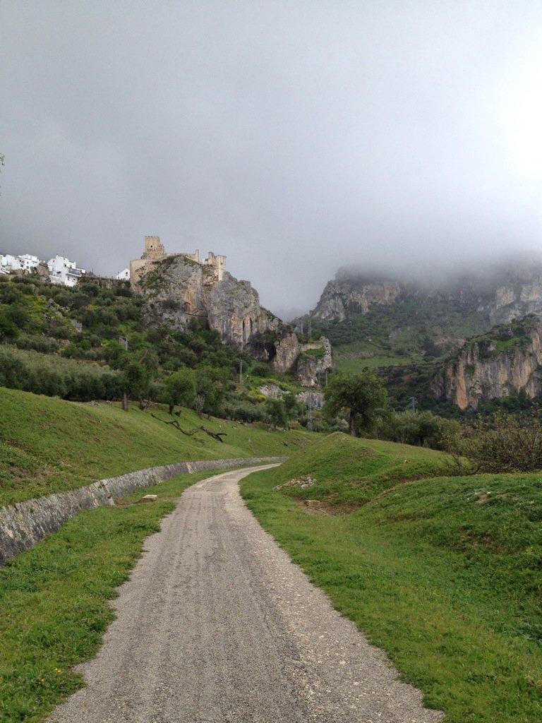 Zuheros. Der Bahntrassenradweg führt direkt auf ein Schloss zu. Wolken hängen in den Bergen.